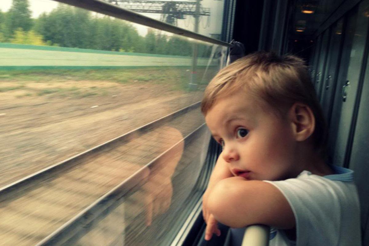 Ребенок в поезде смотрит в окно
