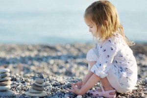 девочка на пляже с галькой